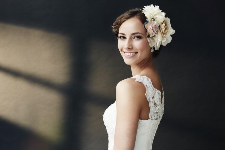 Brautfrisur mit Stoffblume und dunklem Haar
