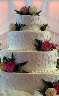 weiße Torte mit gelben und rosa Rosen als farbliche Akzente