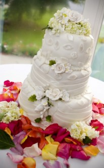 dezente Hochzeitstorte in Weiß mit bunten Blüten angerichtet