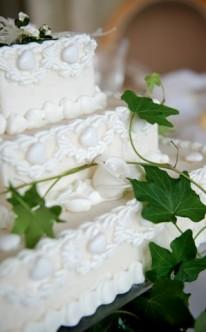 grüner Efeu dekoriert die weiße Torte