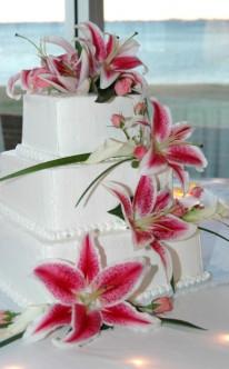 pinke Lilien zieren die weiße Hochzeitstorte