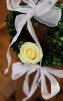 Kirchendekoration mit Kranz und gelber Rose