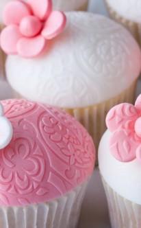 Muffins mit rosa und weißen Zuckerblüten dekoriert