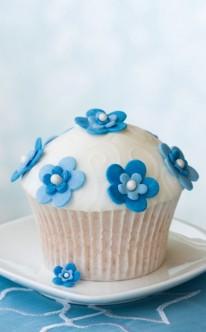 blaue Zuckerblüten zieren den weißen Muffin