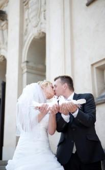 Brautpaar hält zwei weiße Tauben in den Händen