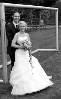 Paar in beliebter Pose vor einem Fußballtor
