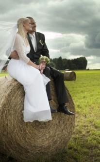 Brautpaar sitz nebeneinander auf einem Heuballen
