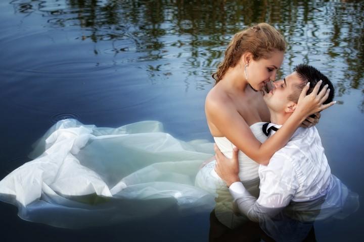 Hochzeitspaar küsst sich im Wasser