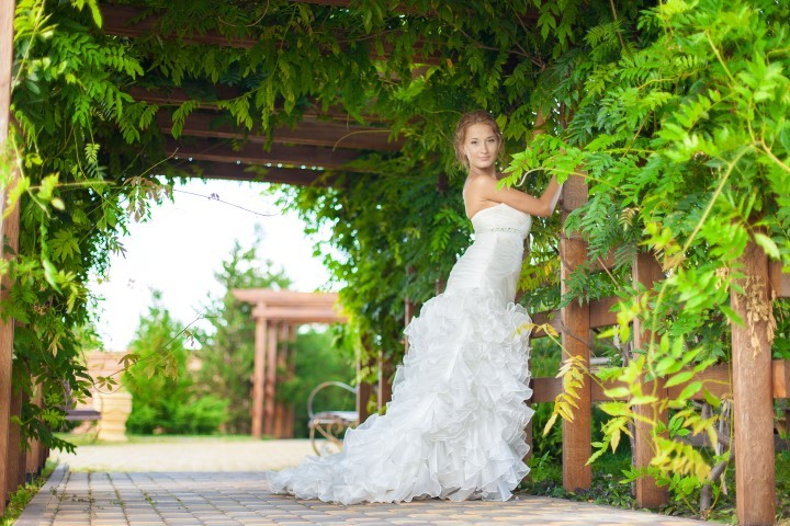 wedding: beautiful young bride posing in green leaves