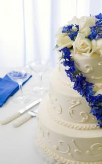 blauer Blütenschmuck auf weißer Torte
