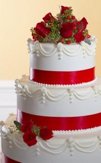 weiße Sahnetorte mit roten Bändern