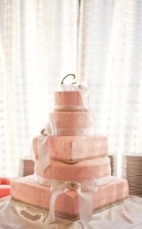 rosa Hochzeitstorte mit weißen Schleifen dekoriert