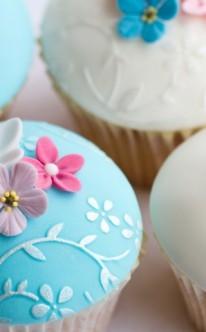 pastellfarbene Blüten dekorieren blaue und weiße Muffins