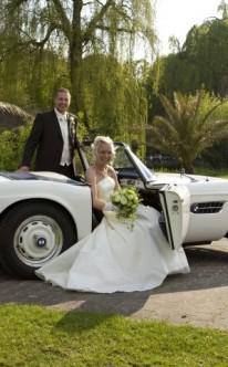 Brautpaar in einem weißen Sportwagen