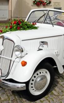 weißer Oldtimer mit roten Rosen geschmückt