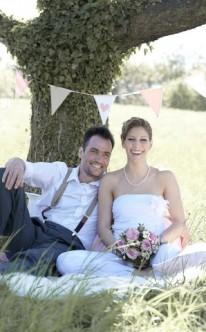 gemeinsam sitzt das Brautpaar unter einem Baum