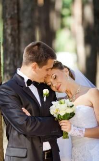 Braut legt den Kopf auf die Schulter ihres Bräutigams